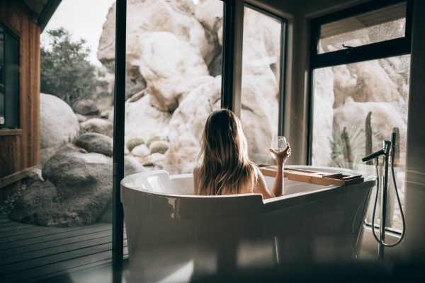 woman in a spa tub overlooking rock formations outside