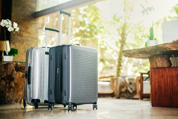 wellness essentials packed in two gray large suitcases stand in the lobby of the hotel