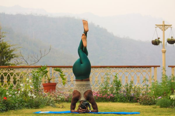 woman practicing different yoga styles outside with mountains in the background