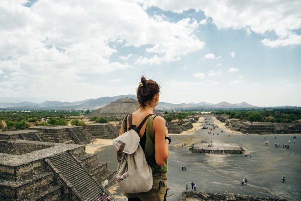 tourist hiking enjoys the view from the top of the Moon Pyramid. The Sun Pyramid and Avenue of the Dead can be seen in the distance in Teotihuacan, Mexico.
