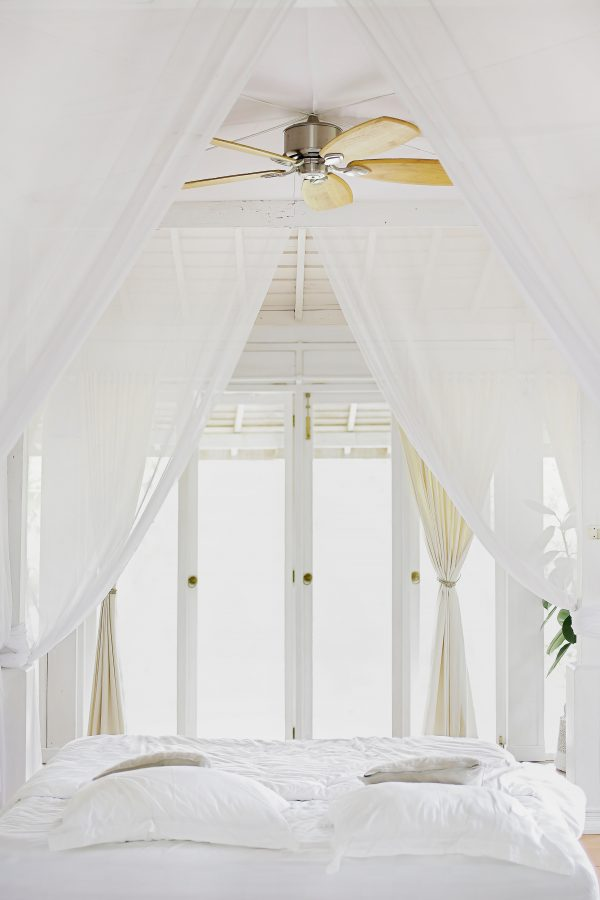 beautiful white room with bed encouraging less stress and more sleep