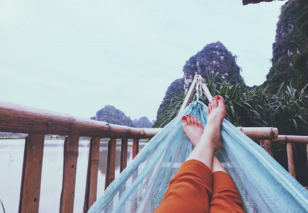 girl managing anxiety during stressful times by relaxing in a hammock