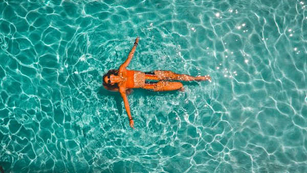 woman floating in a pool enjoying her wellness retreat or vacation destination