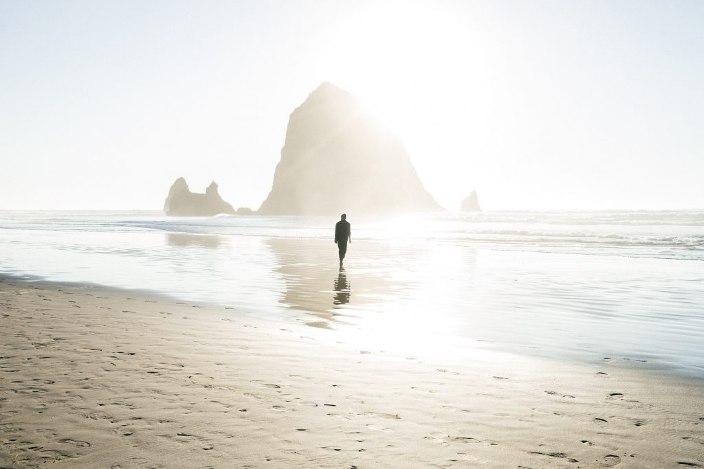 man walking along cannon beach destination in oregon