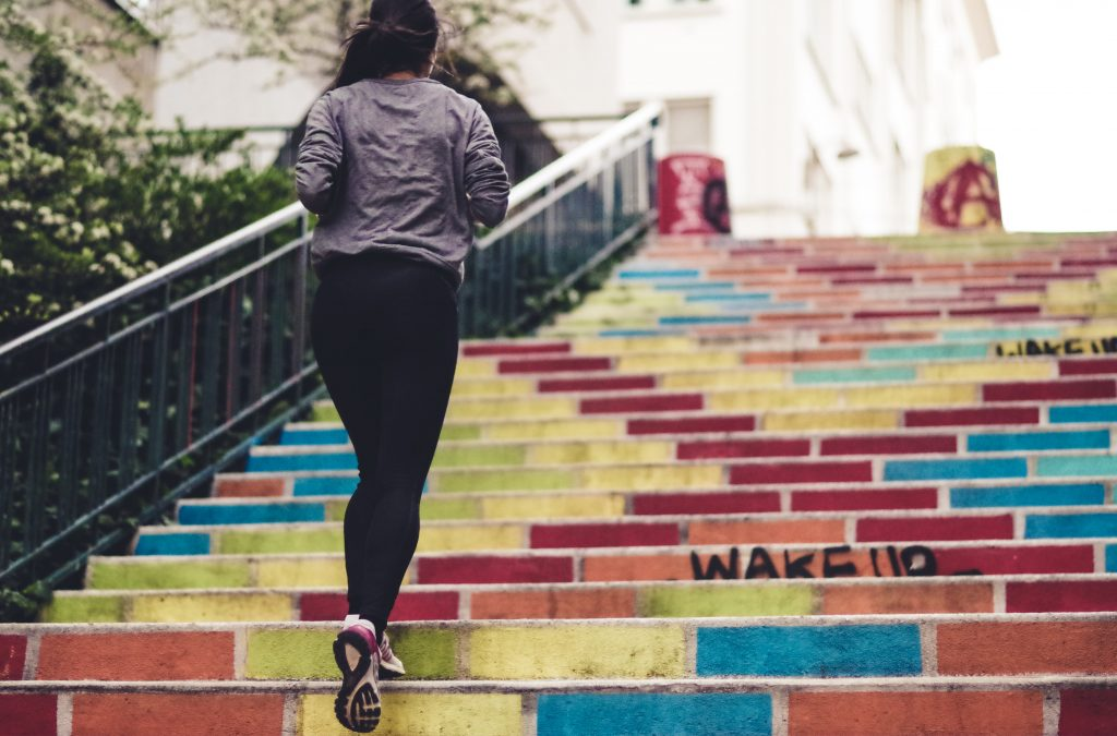 Woman running up the stairs - Top 7 Tips to Stay Active