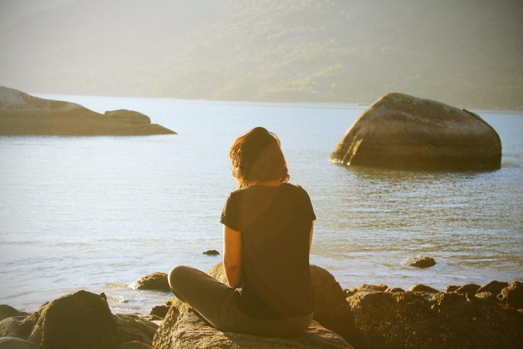 a woman reflecting by the water - loving-kindness meditation