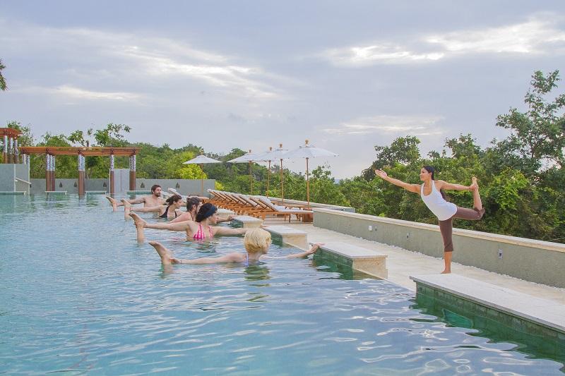 teacher leading yoga in the pool at kamalaya - winter getaway