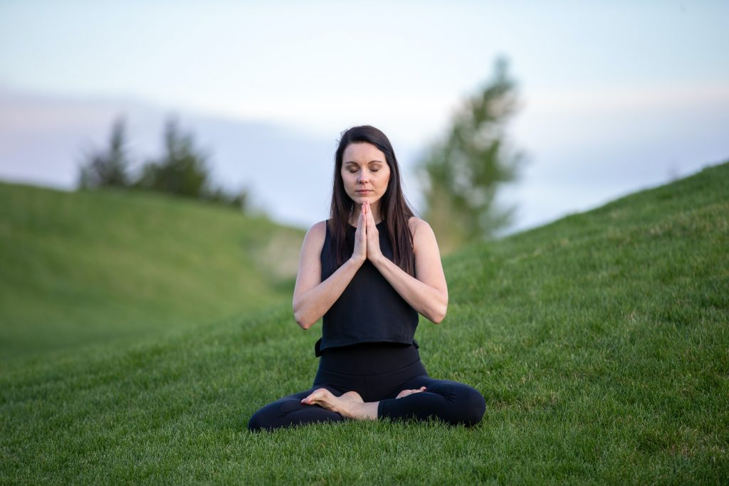 woman meditating outdoors in the grass