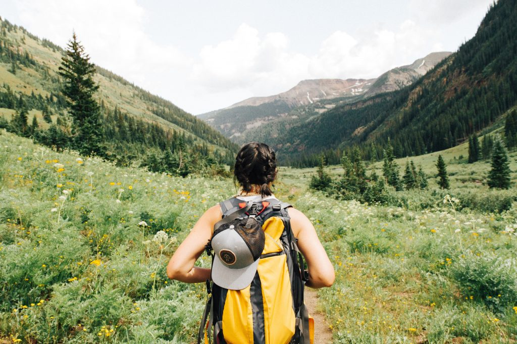 Woman backpacking in a field of green - plant-based traveler