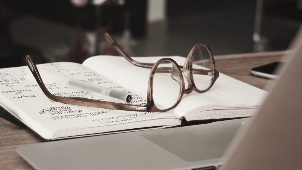 Glasses on a notebook to research where to go before the trip