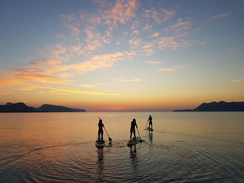 Three travelers paddle boarding into the sunset at Ultimate fitness - winter getaway
