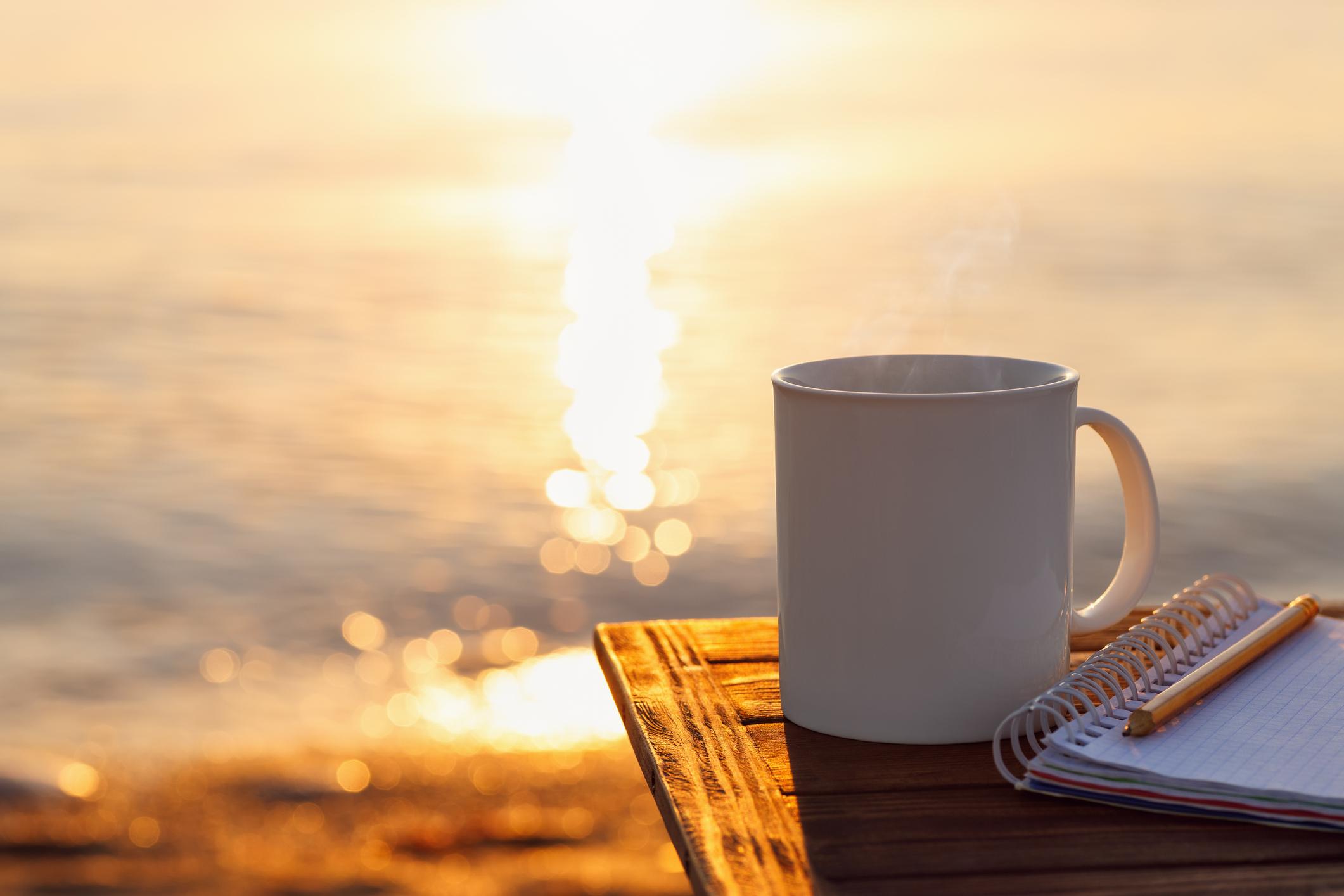 Mug of coffee and journal on table