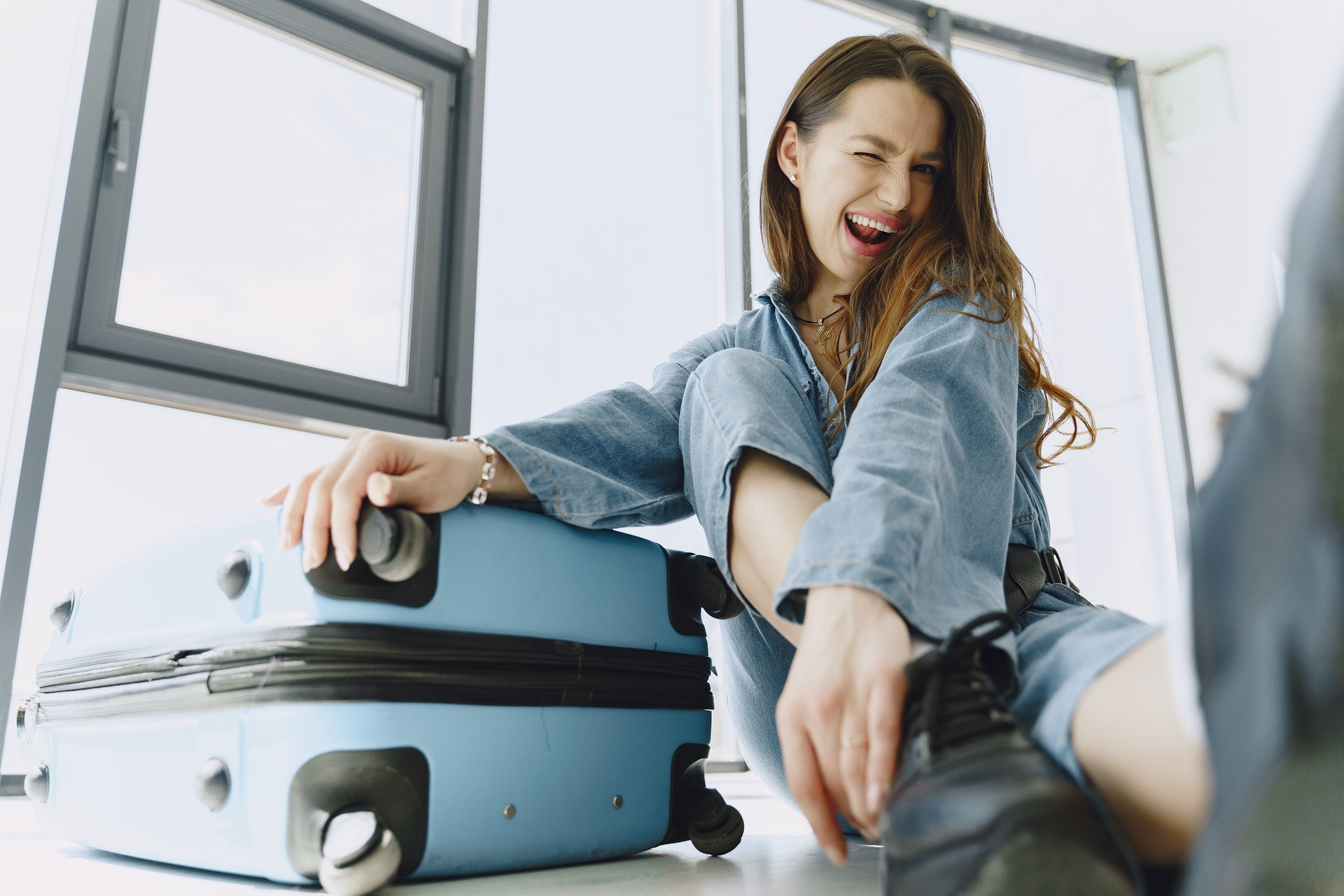 Stress-free travel woman happy with suitcase